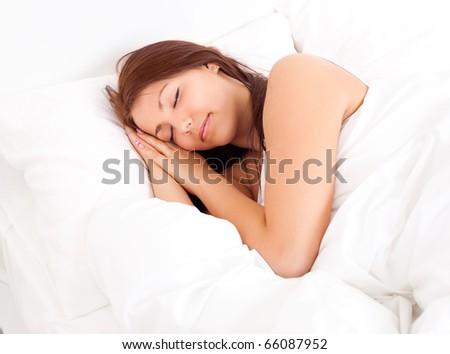 pretty brunette girl sleeping on the white linen - stock photo