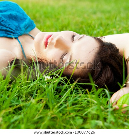 Pretty brunette girl wearing elegant dress relaxing outdoor in green grass and smells aromatic lemon or lime citrus