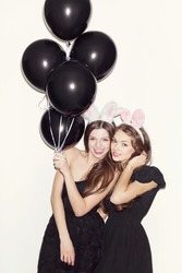 Pretty brunette girls with bunny ears and pink lips having fun. One holding black balloons in her hand. Both looking at camera and smiling. Inside