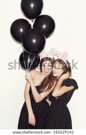 Pretty brunette girls with bunny ears and pink lips having fun One holding black balloons in her hand Both looking at camera and smiling Inside