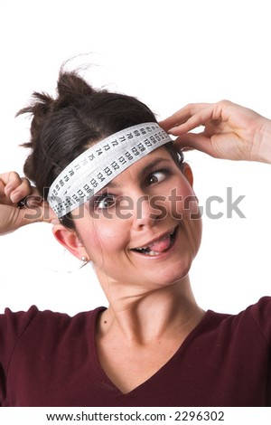 Pretty brunette holding a measuring tape around her head and pulling a face with her tongue out - stock photo