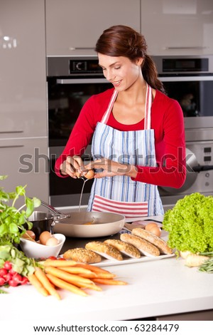 Pretty brunette in the kitchen baking an egg in the frying pan