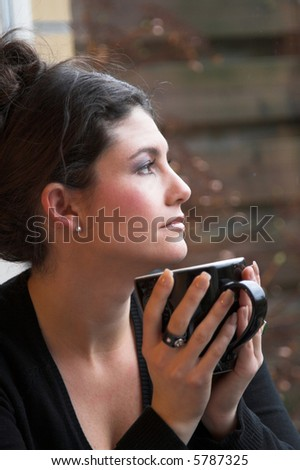 Pretty brunette looking out of the window holding a cup of tea - stock photo