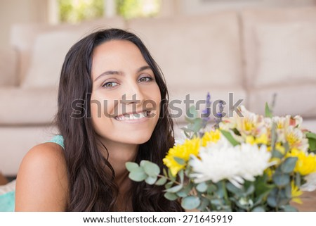 Pretty brunette lying on the floor and smelling the flowers at home in the living room #271645919