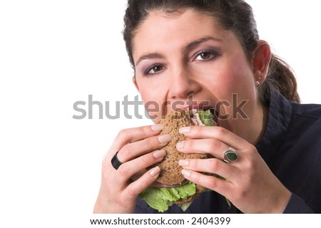 Pretty brunette taking a big bite out of her healthy sandwich