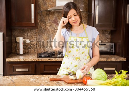 Pretty brunette wearing an apron cutting some onions in the kitchen and crying
