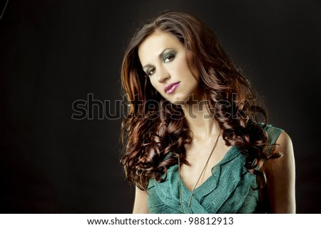 pretty brunette wearing green fashion dress on black background