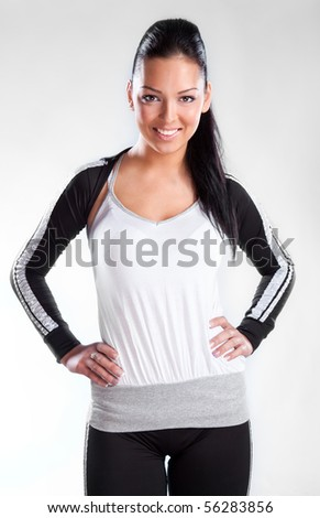 Pretty brunette wearing sport outfit and looking down, studio shot