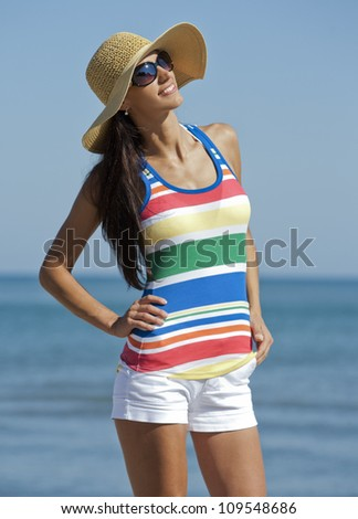 pretty brunette wearing summer outfit on the beach