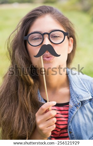 Pretty brunette with fake mustache on a sunny day