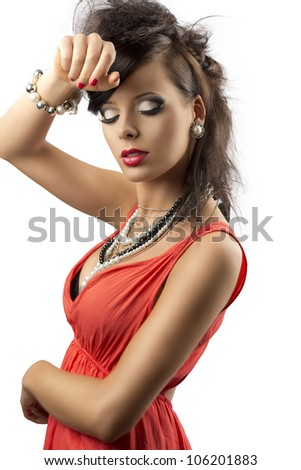 pretty brunette with fashion hair style, red dress and some necklaces. Her body is turned in profile, she looks down and her right hand is on her front