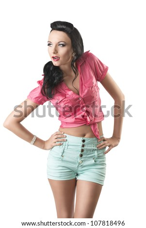 pretty brunette with green shorts and pink shirt, she is in front of the camera with both hands on her hips, she looks at right
