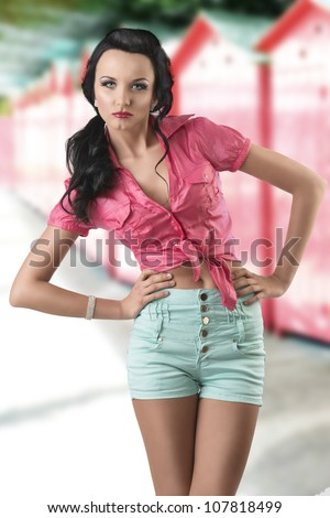 pretty brunette with green shorts and pink shirt, she is inclined at right with both hands on her hips, and looks in to the lens