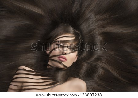 pretty brunette with long  hair laying down and some locks on the face and the neck