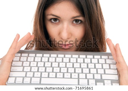Pretty brunette woman holds wireless laptop computer keyboard and looking at the camera isolated on a white background