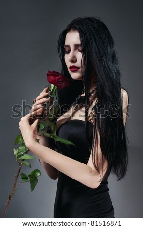 Pretty brunette woman in black dress with red rose