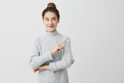 Pretty brunette woman posing on camera with tricky look and gesturing to side. Female designer presenting lovely product with index finger. Gesture concept