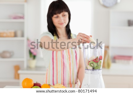 Pretty brunette woman putting vegetables in a mixer while standing in the kitchen