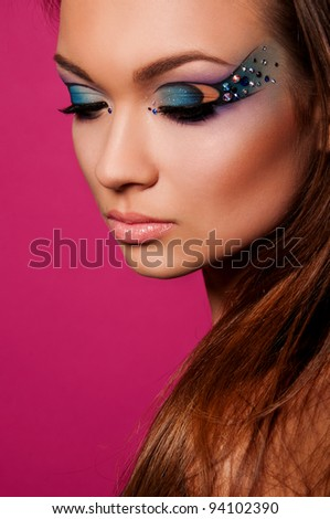 pretty brunette woman with creative makeup on pink background