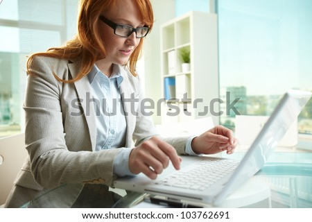 Pretty business lady working on laptop in office