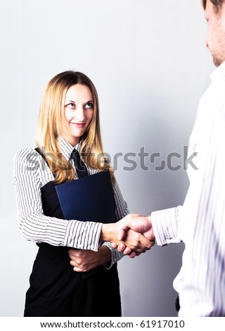 Pretty business woman shaking hands with a man in her office