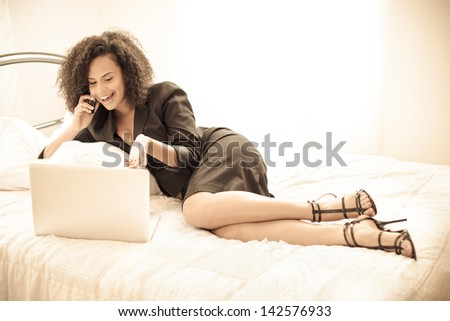 Pretty business woman smiling on her cell phone and computer