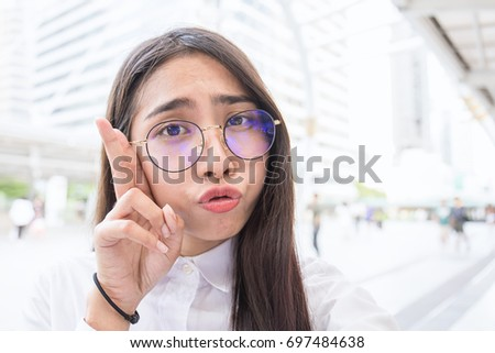 Pretty business woman take a self portrait with her smart phone outside, Asian nerdy glasses girl selfie over building background