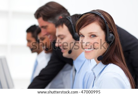 Pretty businesswoman and her team working in a call center in a company