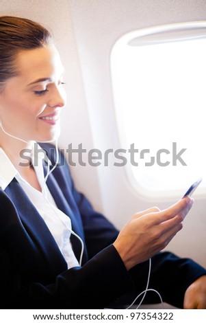 pretty businesswoman listening music on airplane
