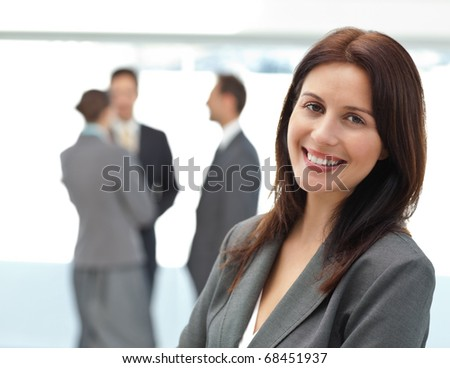 Pretty businesswoman posing in front of her team while working in the background