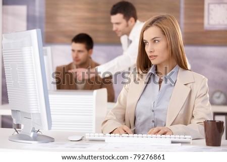 Pretty businesswoman sitting at desk, working on computer, team working in background.?