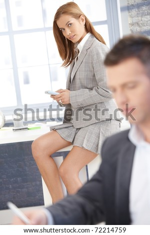 Pretty businesswoman sitting on desk in bright office, texting, businessman working in background.?