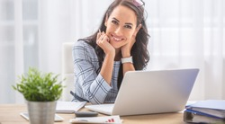 Pretty businesswoman smiles at the camera while sitting at her desk in front of the computer.