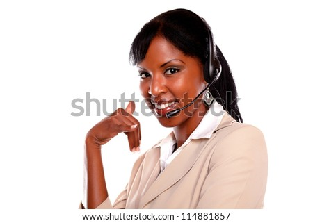 Pretty call center employee smiling at you while wearing her headset against white background