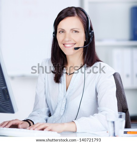 Pretty call center operator typing on the keyboard at her table