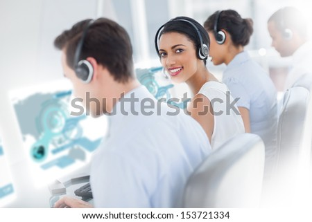 Pretty call center worker using futuristic interface hologram smiling at camera in office