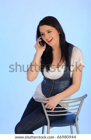 Pretty casual woman speaking on the phone sitting on the chair