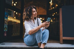 Pretty Caucaisan woman with modern cellphone device in hands resting at touristic street sitting outdoors and smiling, charming hipster girl holding smartphone technology for network and looking away