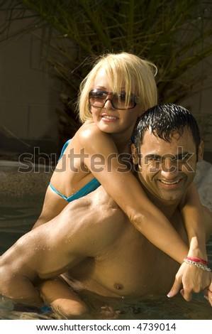 Pretty Caucasian blond in bikini hangs on to smiling Hispanic man in backyard swimming pool