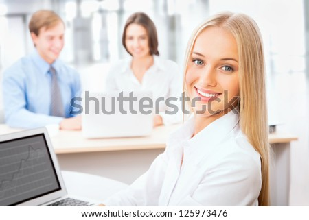 Pretty Caucasian business woman at office with colleagues on the background
