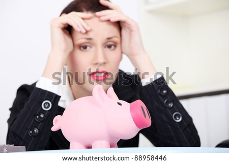 Pretty caucasian businesswoman in depression with piggy bank.