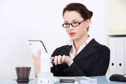 Pretty caucasian businesswoman using a tablet in the office.