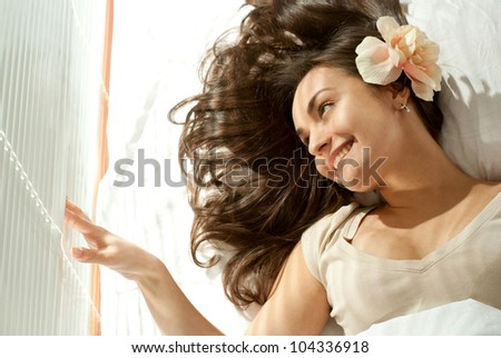 Pretty Caucasian girl lying on a pillow on a light background