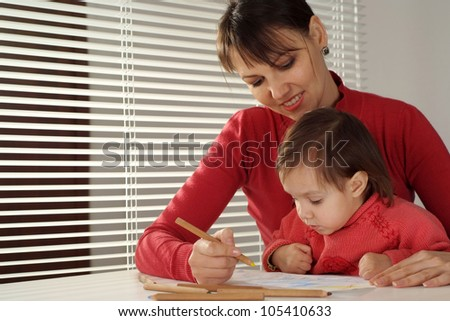Pretty Caucasian happy mom with a daughter draw with pencils on dark background
