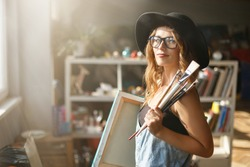 Pretty caucasian long-hair female artist in cute black hat and eyeglasses holding brush and canvas in light contemporary studio