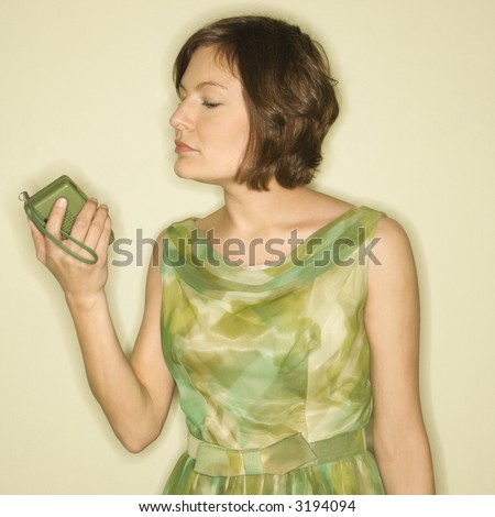 Pretty Caucasian mid-adult woman wearing green vintage dress looking at handheld radio.