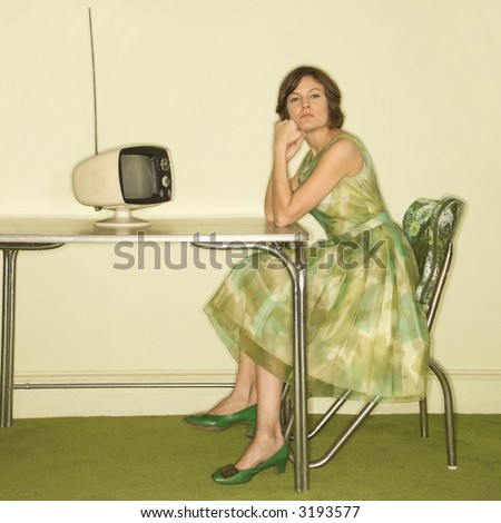 Pretty Caucasian mid-adult woman wearing green vintage dress sitting at 50\'s retro dinette in front of old televsion looking bored.