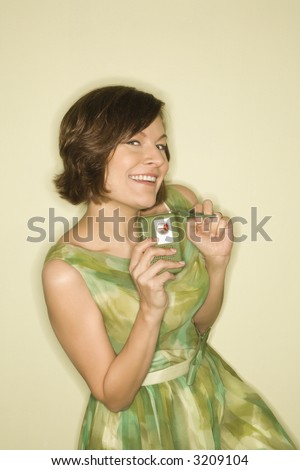 Pretty Caucasian mid-adult woman wearing green vintage dress with handheld radio smiling at viewer.
