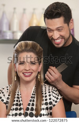 Pretty Caucasian woman and bearded hair stylist smiling