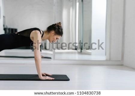 Pretty Caucasian woman doing pilates exercise on mat. #1104830738